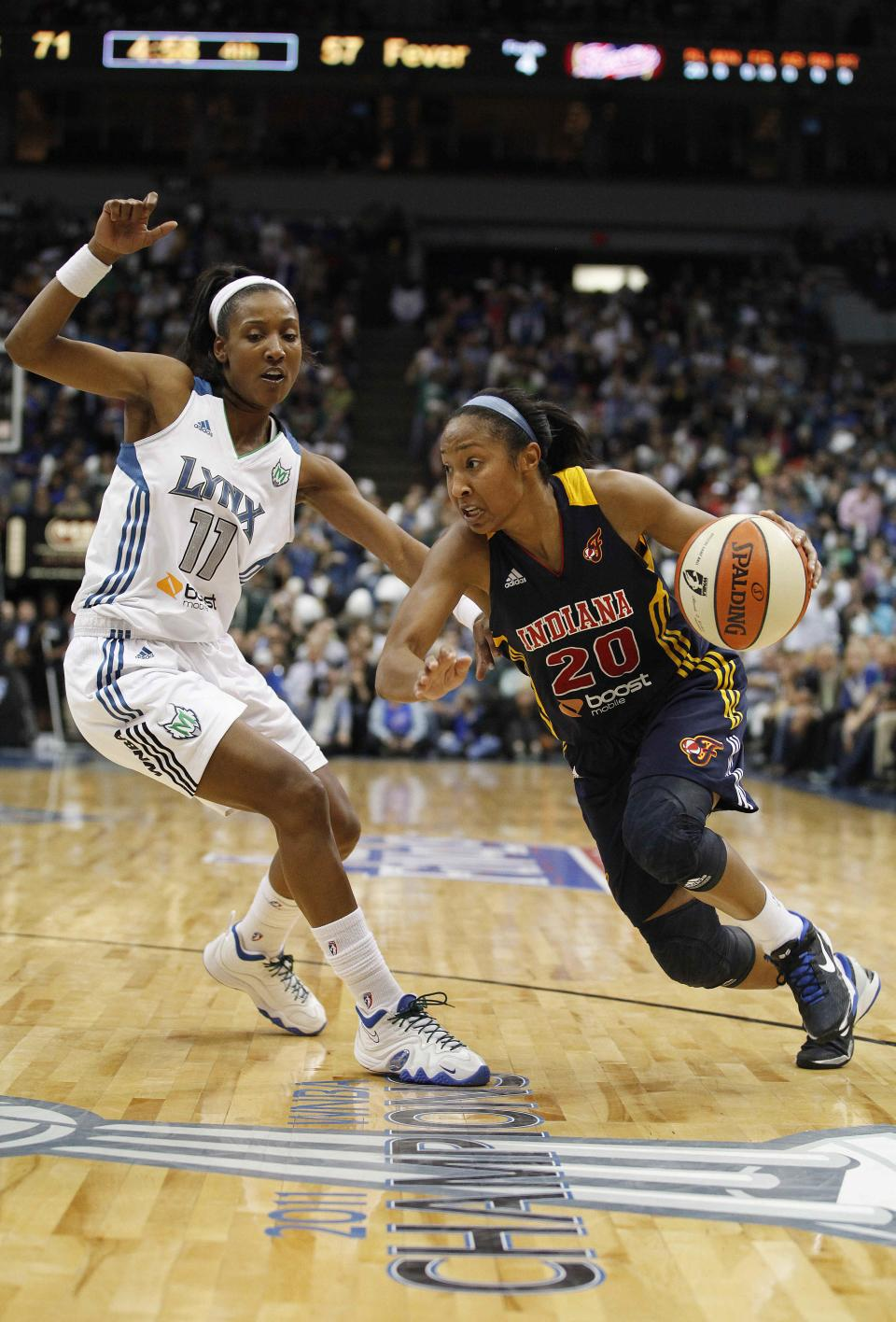 Indiana Fever guard Briann January (20) drives the ball past Minnesota Lynx guard Candice Wiggins (11) in the second half of Game 2 of the WNBA basketball Finals Wednesday, Oct. 17, 2012, in Minneapolis. The Lynx won 83-71. (AP Photo/Stacy Bengs)