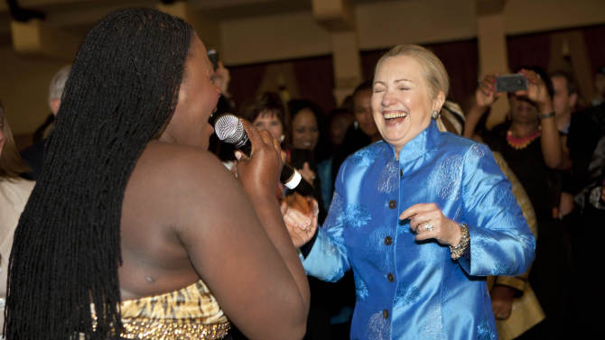 FILE - In this Aug. 7, 2012, file photo, U.S. Secretary of State Hillary Rodham Clinton laughs as South African jazz singer Judith Sephuma, left, invites her to dance to African music at a gala dinner at Sefako M. Makgatho Presidential Guest House in Pretoria, South Africa. Clinton's plan for 2013 was simple. She'd embark on an epic swansong around the world as secretary of state, a dizzying itinerary of east-west and north-south flights that would take her past 1 million miles in the air at the helm of American diplomacy and perhaps break her own record of 112 countries visited while in the post. Her health got in the way and she was sidelined by circumstances beyond her control. (AP Photo/Jacquelyn Martin, Pool)