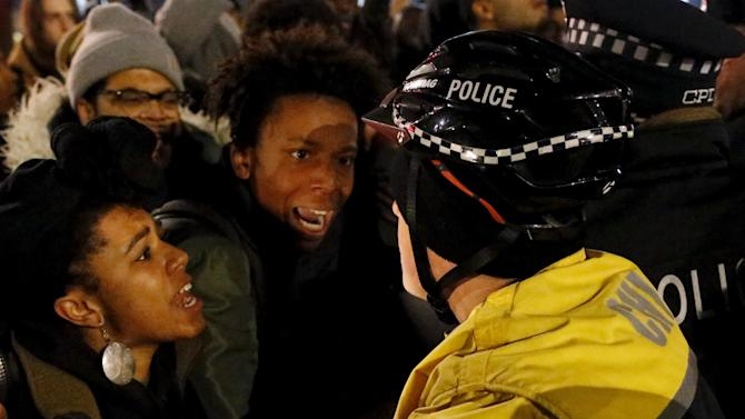 Demonstrators scuffle with a police officer during protests in Chicago, Illinois