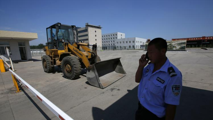 A policeman talks on his mobile phone as he guards a gate outside the Xinming Steel Pipe Plant in Tangshan