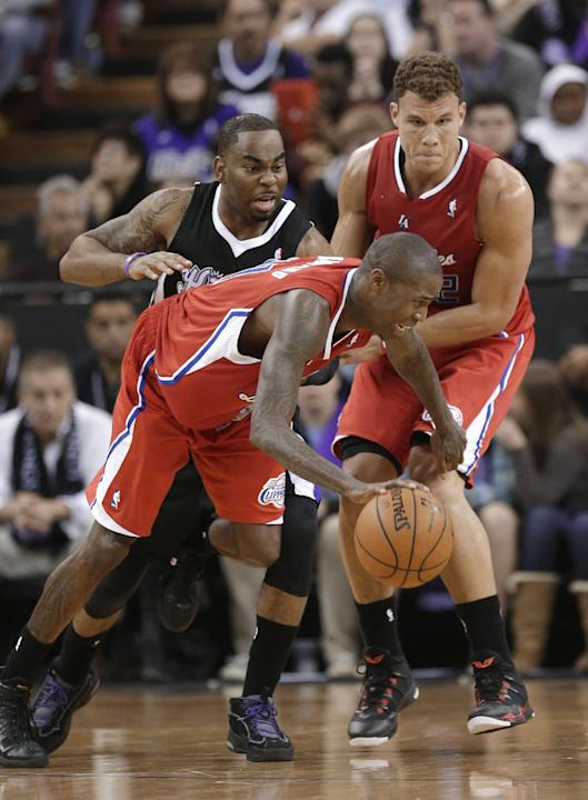 Los Angeles Clippers guard Jamal Crawford, center, uses a screen set by teammate Blake Griffin, right, to rid himself of Sacramento Kings guard Marcus Thornton during the fourth quarter of an NBA bask