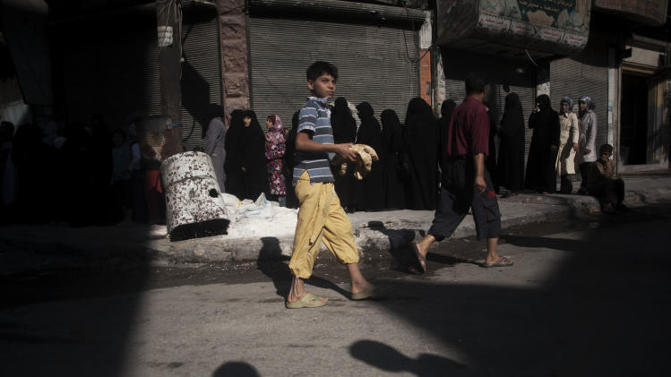 In this Saturday, Sept. 22, 2012 photo, a Syrian boy carries loaves of bread while women stand in line to buy bread outside of a bakery in the Saif al Dawla neighborhood of Aleppo, Syria, Friday, Sept. 21, 2012. (AP Photo/ Manu Brabo)