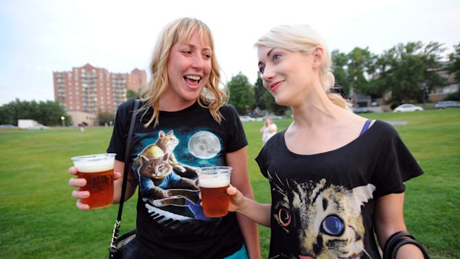 """Lori Priefer, left, and Jessa Alt, both of Minneapolis, talk about their cat themed shirts after arriving at the Walker Art Center for the first """"Internet Cat Video Film Festival,"""" showcasing the best of cat films on the Internet in Minneapolis Thursday Aug. 30, 2012. The Walker Art Center in Minneapolis held its first-ever online cat video festival, a compilation of silly cat clips that have become an Internet phenomenon, attracting millions of viewers for some of the videos. (AP Photo/Craig Lassig)"""