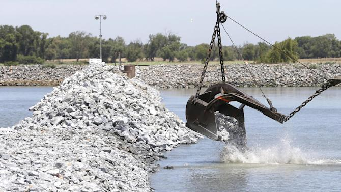 A load of rocks are placed during the construction of a temporary emergency barrier to block salt water intrusion into the West False River in the Sacramento-San Joaquin Delta near Oakdale, Calif., Friday, May 29, 2015.  About 150,000 tons of been used in the construction of the nearly 750-foot-wide barrier, built between Jersey and Bradford Islands by the California Department of Water Resources.  The project, which is nearing completion nearly two weeks ahead of schedule, will be removed in mid-November.  As less fresh water flows down the rivers, due to California's historic drought, salt salt water moves farther up the delta which effects the water supply to communities and irrigation water for farmers.(AP Photo/Rich Pedroncelli)