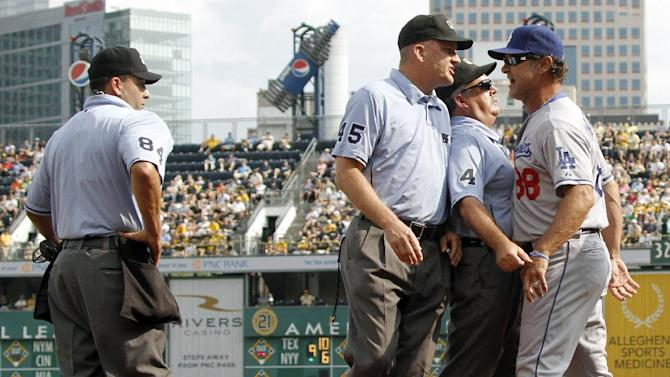 Umpires Tim Tschida (4) and Jeff Nelson (45) get in front of Los Angeles Dodgers manager Don Mattingly (88) as he yells at home plate umpire Angel Vampos (84) after he was ejected in the second inning of the baseball game against the Pittsburgh Pirates on Thursday, Aug. 16, 2012, in Pittsburgh. (AP Photo/Keith Srakocic)