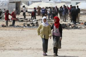 Syrian refugees girls walk in front of the remains …