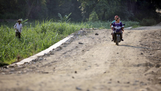 In this May 25, 2012 photo, women ride a motorcycle on an unfinished road connecting to Myanmar side in Ruili, Yunnan Province, China. This remote southwestern Chinese city of about 140,000 nestled in a river valley on the Myanmar border amassed huge wealth over decades of trade and smuggling of drugs, timber and jade. Now, China's main trading gateway to its long-isolated neighbor is waiting for a new boom that may never come. (AP Photo/Eugene Hoshiko)