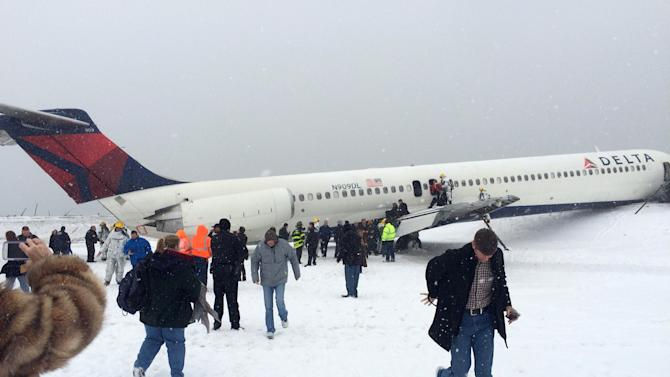 In this photo provided by passenger Amber Reid, passengers are evacuated after a Delta plane skidded off the runway while landing at LaGuardia Airport during a snowstorm, Thursday, March 5, 2015, in New York. Authorities said the plane, from Atlanta, carrying 125 passengers and five crew members, veered off the runway at around 11:10 a.m. before crashing through a chain-link fence and coming to rest with its nose perilously close to the edge of an icy bay. (AP Photo/Amber Reid)