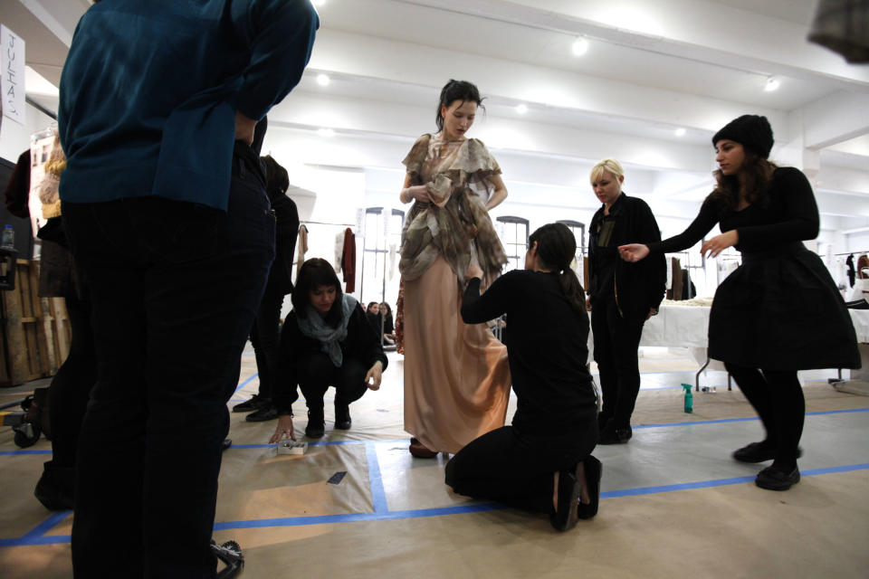 A model has her outfit checked before the Rodarte fall 2012 collection show during Fashion Week, Tuesday, Feb. 14, 2012, in New York. (AP Photo/Jason DeCrow)