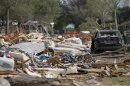 Debris from destroyed housing complex lies near damaged vehicle, next to site of deadly fertilizer plant explosion in West
