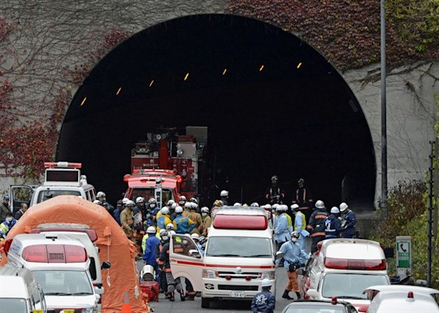 Police officers and firefighters gather at the exit of the Sasago Tunnel on the Chuo Expressway in Otsuki, Yamanashi Prefecture, central Japan, Sunday morning, Dec. 2, 2012. Police said that parts of