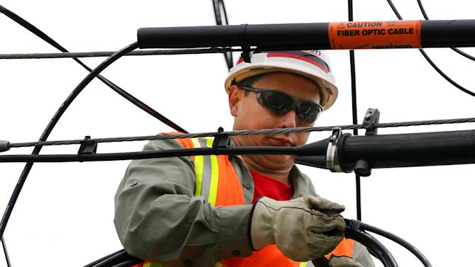 FILE - In this May 11, 2006, file photo,Verizon lineman Clemente Calma installs fiber optic cable on a telephone pole in Massapequa Park, N.Y. Verizon is rapidly replacing copper phone lines with lower-maintenance fiber-optic cables. (AP Photo/Mark Lennihan, File)