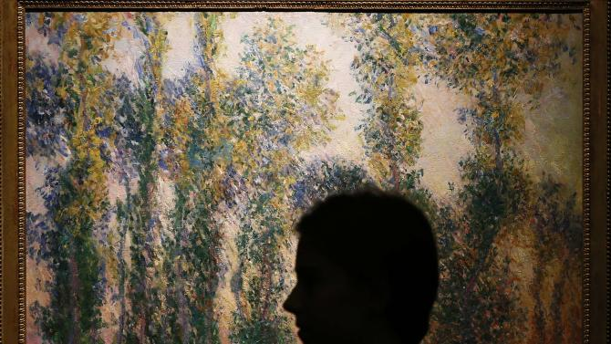 "A woman poses in front of ""Les Peupliers a Giverny"", painted by Claude Monet, at Sotheby's preview in London"