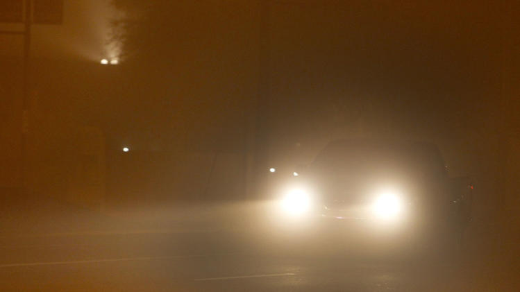 A truck tries to drive through a dust storm in downtown Phoenix, Tuesday, July 5, 2011. (AP Photo/Ross D. Franklin)