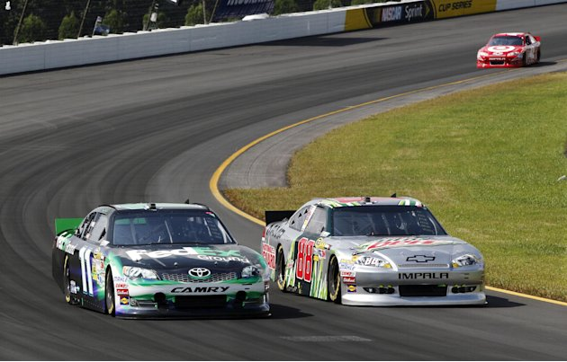 Dale Earnhardt Jr., (88) races side-by-side with Denny Hamlin (11) as Juan Pablo Montoya (42) follows during the NASCAR Sprint Cup Series auto race, Sunday, Aug. 5, 2012, at Pocono Raceway in Long Pon