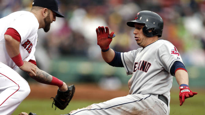 Cleveland Indians' Asdrubal Cabrera, right, slides safely back to first base after rounding on a single as Boston Red Sox first baseman Mike Napoli takes the throw during the seventh inning of a baseball game at Fenway Park in Boston, Saturday, May 25, 2013. (AP Photo/Winslow Townson)