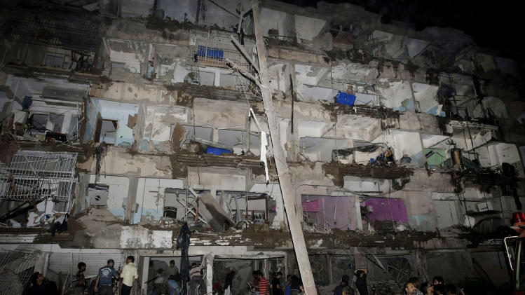 Pakistanis gather at the site of a bomb blast in Karachi, Pakistan, Sunday, March 3, 2013. Pakistani officials say a bomb blast has killed dozens of people in a neighborhood dominated by Shiite Muslims in the southern city of Karachi. (AP Photo/Fareed Khan)