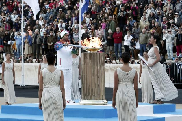Greek figure skater Markouzios lights an altar with an Olympic torch of the Sochi 2014 Winter Games during a handover ceremony in Athens