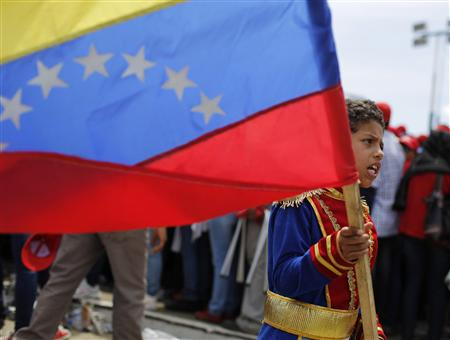 A boy dressed as a soldier from colonial period carries the national flag in a crowd of supporters of Venezuela's late President Hugo Chavez at the Military Academy in Caracas, March 7, 2013. REUTERS/Tomas Bravo