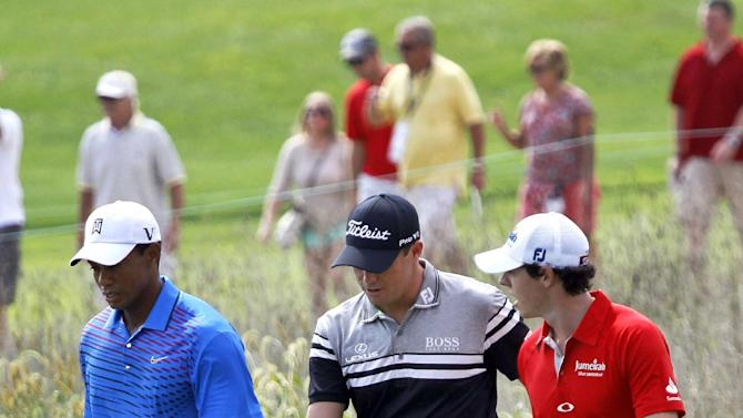 The threesome of Tiger Woods, left, Nick Watney, center and Rory McIlroy of Northern Ireland, head out on the 11th fairway during the first round of the BMW Championship PGA golf tournament at Crooked Stick Golf Club in Carmel, Ind., Thursday, Sept. 6, 2012. (AP Photo/Charles Rex Arbogast)