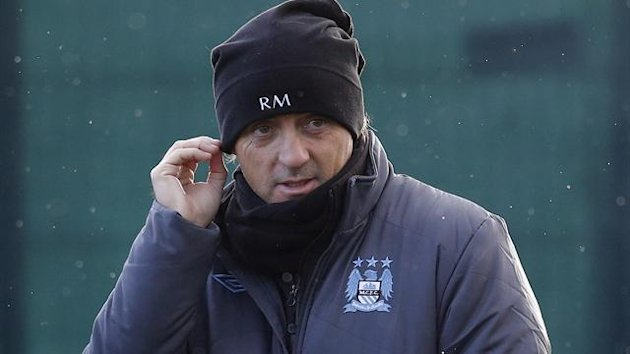 Manchester City manager Roberto Mancini adjusts his hat as he watches his players during a training session at the club&#39;s Carrington training complex in Manchester (Reuters)