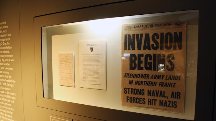 This Aug. 4, 2012 photo shows  a newspaper announcing that Eisenhower's army had landed on Normandy and the liberation of Europe was under way at the Eisenhower Presidential Library and Museum in Abilene, Kan. A new World War II exhibit starting this summer at the Eisenhower Presidential Library and Museum will pay tribute to the millions who fought, but organizers also have another purpose for the ambitious three-year project: getting young people engaged in the war's relevance.  (AP Photo/John Milburn)