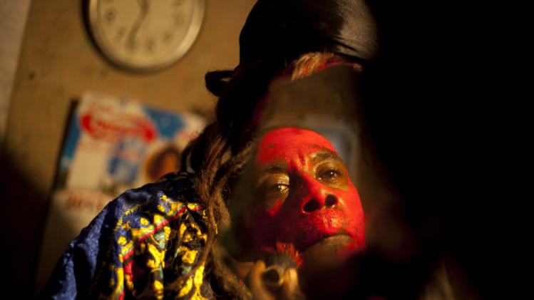 In this Jan. 27, 2013 photo, snake handler Saintilus Resilus looks in the mirror as he paints his face red before performing with snakes for money during the pre-Lenten Carnival season at his home in Petionville, Haiti. It's the serpents that help him eat and pay rent, in addition to his work for a neighborhood herbologist. And it's the snakes for which he's most famous. (AP Photo/Dieu Nalio Chery)
