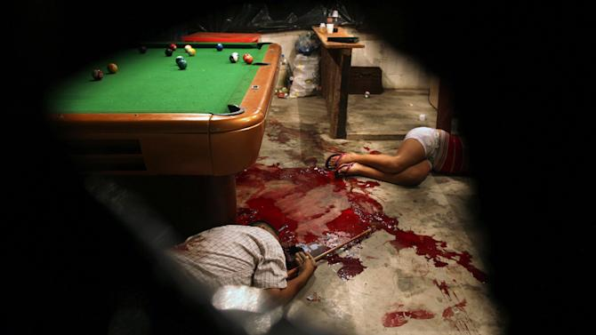 FILE - In this March 11, 2012 file photo, the bodies of Lesbia Altamirano and Wilmer Orbera lie on the floor of a pool hall after they wre attacked by masked assailants in Choloma, on the outskirts of San Pedro Sula, Honduras. Global murder rates have declined slightly, but remain very high in the Americas and parts of Africa, according to a new U.N. study released Thursday, April 10, 2014. That comes as no news to the city of San Pedro Sula, long considered the most violent city in Honduras, the country that has the highest murder rate in the world. (AP Photo/Esteban Felix, File)