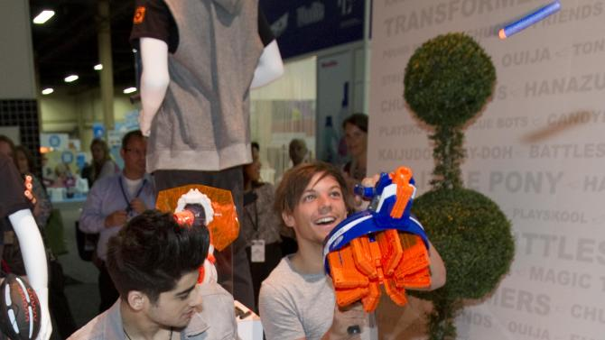 COMMERCIAL IMAGE –  CAPTION CHANGE FROM HARRY STYLES TO LIAM PAYNE - Members of the pop band One Direction, Zayn Malik, left, and Liam Payne, visit Hasbro at Licensing Expo 2012 to try out the new NERF N-Strike Elite Hail-Fire Blaster on Tuesday, June 12, 2012 in Las Vegas. Hasbro and One Direction have teamed up to launch a new line of toys and games this fall based on the members of the popular boy band. The NERF Hail-Fire Blaster is the highest performing NERF blaster to date, holding a maximum capacity of 144 darts and firing up to 75 feet.  (Photo by Eric Jamison/Invision for Hasbro/AP Images)