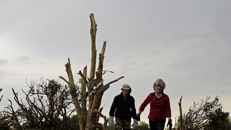 Lea Bessinger and her son Josh Bessinger look through the rubble of the elder Bessinger's tornado-ravaged home Tuesday, May 21, 2013, in Moore, Okla. A huge tornado roared through the Oklahoma City suburb Monday, flattening an entire neighborhoods and destroying an elementary school with a direct blow as children and teachers huddled against winds. (AP Photo/Charlie Riedel)