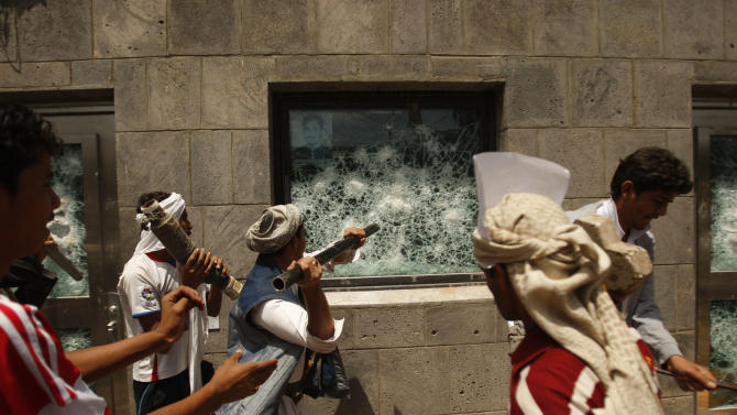 FILE - In this Thursday, Sept. 13, 2012 file photo, Yemeni protesters break a window of the U.S. Embassy during a protest about a film ridiculing Islam's Prophet Muhammad, in Sanaa, Yemen. U.S.-funded ads on Pakistani television include President Barack Obama extolling America's religious tolerance. To many in the Muslim world, this misses the mark in efforts to calm the outrage over a film mocking the Prophet Muhammad. (AP Photo/Hani Mohammed, FIle)