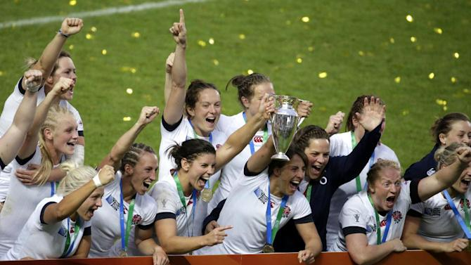 England players celebrate with the trophy after winning the IRB Women's Rugby World Cup final against Canada in Paris on August 17, 2014