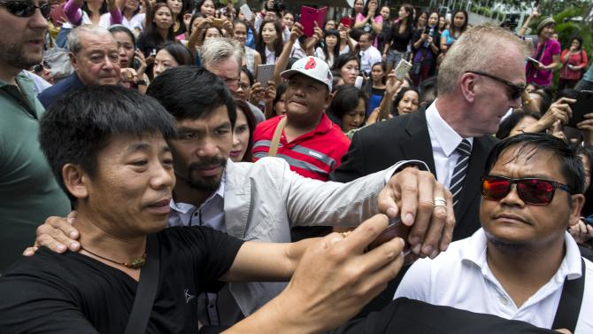 Boxer Manny Pacquiao of the Philippines poses for a selfie with a fan during his tour in Hong Kong