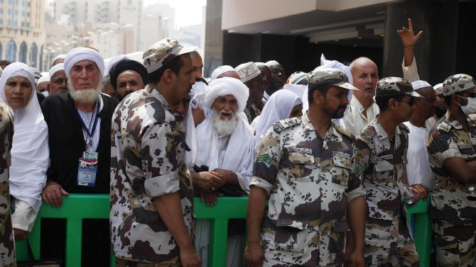 Members of Saudi security forces secure the area as Muslim pilgrims wait to enter the Grand mosque during Friday prayers in Mecca