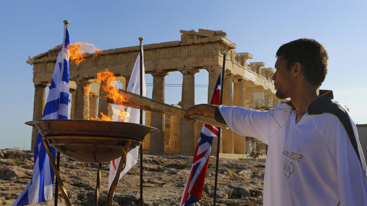 FILE - The May 16, 2012 file photo shows torchbearer Dimitrios Chondrokoukis, a Greek high jump athlete, lighting a cauldron with the Olympic Flame atop the Athens Acropolis. Chondrokoukis' father confirmed to Greek media Friday, July 26, 2012 that his son failed a doping test.  (AP Photo/Yannis Behrakis/pool)