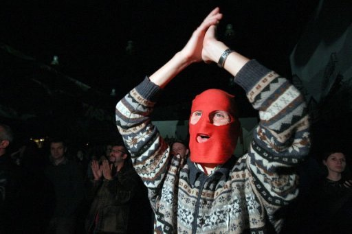 <p>A Russian opposition supporter, wearing a red balaclava, shouts and applauses during a concert in support of Pussy Riot on September 9. The band plans a new protest in Russia despite the jailing of three of its members for a performance against Vladimir Putin in an Orthodox cathedral, band members said.</p>