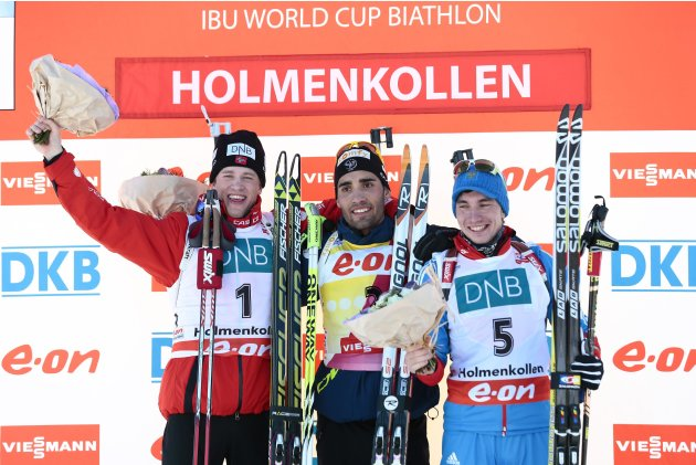 Fourcade of France on the podium flanked by Norway's Boe and Loginov of Russia after the men's 12.5 km pursuit race at the Biathlon World Cup in Oslo