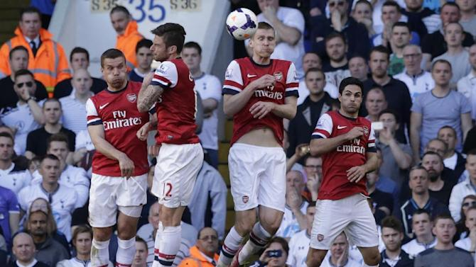 Arsenal's players from the left, Lukas Poldoski, Oliver Giroud, Per Mertesacker and Mikel Arteta jump together as they defend against a direct free kick during the English Premier League soccer match between Tottenham Hotspur and Arsenal at White Hart Lane stadium in London, Sunday, March 16, 2014