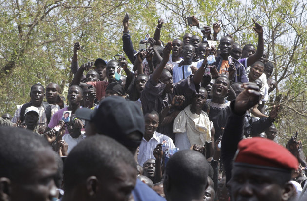 Supporters of Senegalese President Abdoulaye Wade, unseen, cheer outside the polling station where he was voting, in his home Point E neighborhood of Dakar, Senegal Sunday, March 25, 2012. Senegalese voters are deciding Sunday whether to give their 85-year-old president another term in office, or instead back his one-time protege Macky Sall in a runoff election that could oust the incumbent of 12 years.(AP Photo/Rebecca Blackwell)