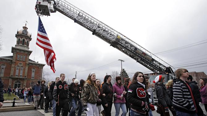 Chardon High School students walk under a large American flag on the town square in Chardon, Ohio Wednesday, Feb. 27, 2013 during a memorial march for 3 students killed in a shooting at the school last year. Students walked from the school to the town square for a memorial commemoration. The march ended at the courthouse where 18-year-old shooter T.J. Lane pleaded guilty to all charges Tuesday. He could face life in prison at his sentencing March 19.(AP Photo/Mark Duncan)