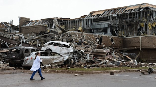 A nurse walks past the destruction at Moore hospital after a huge tornado struck Moore