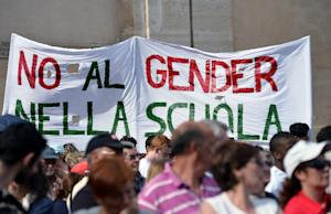 "People hold a banner that reads "" No gender in …"