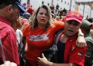A woman is carried out of the crowd of supporters of Venezuela's late President Hugo Chavez standing in line to view his body in state at the Military Academy in Caracas, March 7, 2013. REUTERS/Tomas Bravo