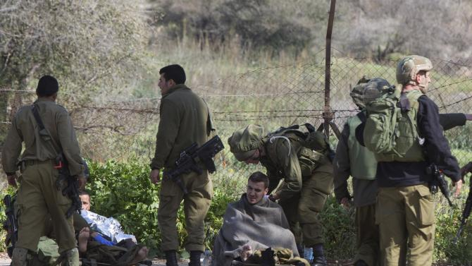 Wounded Israeli soldiers lie on a stretcher near Israel's border with Lebanon