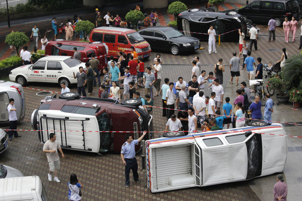 Chinese look at overturned Japanese cars after an anti-Japan protest in Shenzhen, China's Guangdong Province, Sunday, Aug. 19, 2012. Japanese activists swam ashore and raised flags Sunday on an island claimed by both Japan and China, fanning an escalating territorial dispute between the two Asian powers. (AP Photo/Vincent Yu)