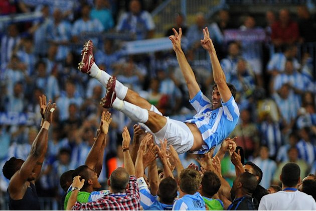 Malaga's Dutch Forward Ruud Van Nistelrooy Being Tossed By His AFP/Getty Images
