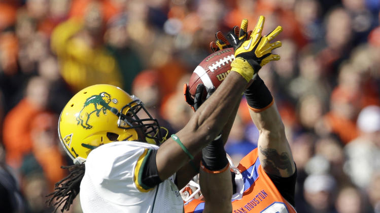 CORRECTS IDS TO NORTH DAKOTA STATE CORNERBACK MARCUS WILLIAMS (1) AND SAM HOUSTON STATE'S TREY DILLER (18), NOT SAM HOUSTON STATE'S RIDGEWAY FRANK (1) AND NORTH DAKOTA STATE'S DEREK MCGINNIS (18) -  North Dakota State cornerback Marcus Williams (1) intercepts a pass intended for Sam Houston State's Trey Diller (18) during the first half of the FCS Championship NCAA college football game, Saturday, Jan. 5, 2013, in Frisco, Texas. Cody Morgan (35) watches on the play. (AP Photo/Tony Gutierrez)