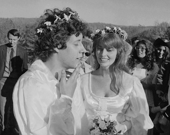 "FILE - This Oct. 9, 1969 file photograph shows performer Arlo Guthrie singing ""Amazing Grace"" to his new bride Jackie Hyde, at their wedding ceremony on Guthrie's farm in Washington, Mass. Folk singer Arlo Guthrie has announced the death of his wife Jackie at age 68. An obituary released by Guthrie's record label says Jackie Guthrie had inoperable cancer and died Sunday, Oct. 14, 2012, at the couple's winter home in Sebastian, Fla. They had recently celebrated their 43rd wedding anniversary. (AP Photo/Steve Starr, file)"