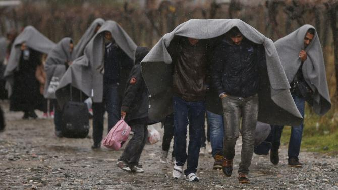 Migrants shield from rain with blankets as they walk after crossing the border from Greece into Macedonia, near Gevgelija