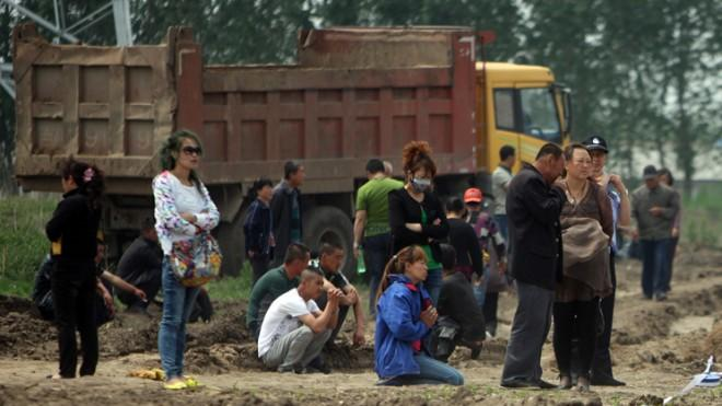Victims' relatives stand outside the scene of a deadly fire at a poultry slaughterhouse inChina on June 3.